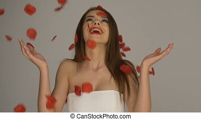 Brunette woman with red rose petals