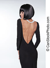 Brunette woman with sexy back in black dress posing at studio. Vogue style. Fashion Haircut.