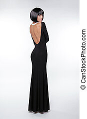 Brunette woman with sexy back in black long dress posing at studio. Vogue style. Fashion Haircut.