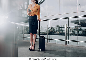 Brunette woman with suitcase is waiting for flight
