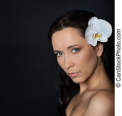 brunette woman with white orchid on black