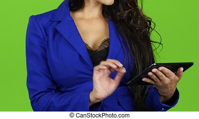 Brunette woman works on tablet, green screen background. Close up
