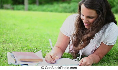 Brunette woman writing on notebooks