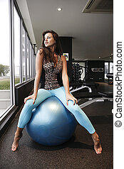 Brunette working out with a blue bouncy ball