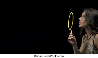 Brunette young girl blowing bubbles on black background