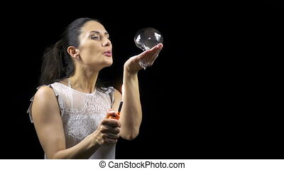 Brunette young woman holding burning soap bubble on black...