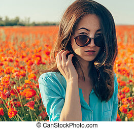 Brunette young woman in sunglasses in spring flowers meadow.