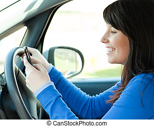 Brunette young woman writing a message sitting in her car