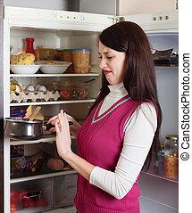 Brunnette woman holding foul food near refrigerator