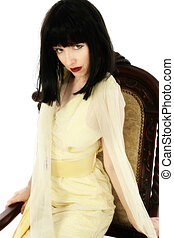 Woman in yellow dress, black hair, sittin in antique chair.