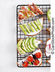 Bruschetta assortment with cream cheese, vegetables, mushrooms and bacon on the lattice