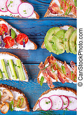 Bruschetta assortment with cream cheese, vegetables, mushrooms and bacon served on the blue wooden table