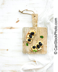 Bruschetta sandwich with brie cheese, honey and blackberry on rustic serving board over white wooden background, top view