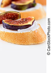 Bruschetta with Fig and Goat Cheese on white background. Shallow depth of field. Selective focus, Closeup