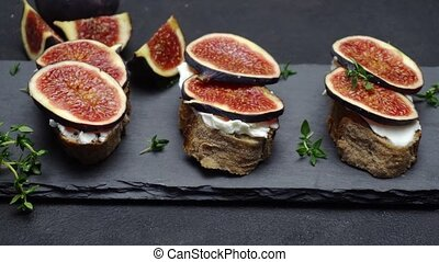 Bruschetta with figs and creme goat cheese on stone serving...