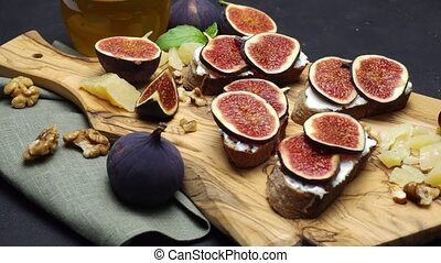 Bruschetta with figs and creme goat cheese on wooden cutting...