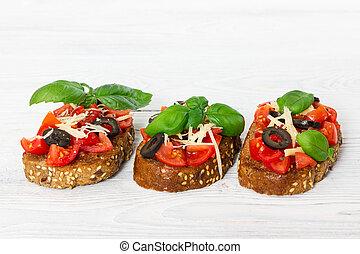 Bruschetta with fresh tomato, basil, cheese and olive