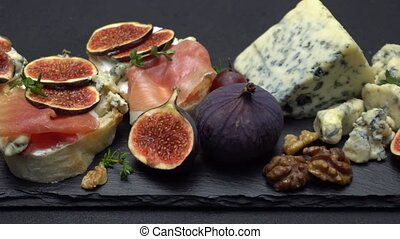 Bruschetta with ham, blue ceese and fresh figs on stone...