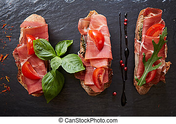 Bruschetta with hamon and sauce on black stone