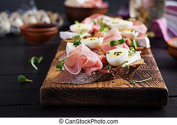 Bruschetta with prosciutto/jamon traditional Italian antipasto. Delicious snack with bread, brie cheese and quails eggs. Health food, tapas