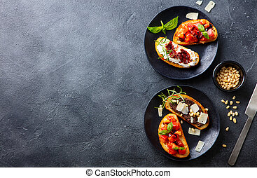 Bruschetta with tomatoes, cheese and olive tapenade on black plates. Grey slate background. Top view. Copy space.