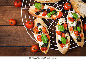 Bruschetta with tomatoes, mozzarella, olives and basil pesto. Top view