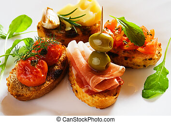 Bruschette, italian toasted bread with prosciutto, olives, tomato and cheese