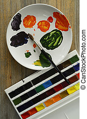 brush and paints on a plate, wooden background