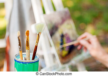 brush for drawing in a glass in the background artist paints a picture