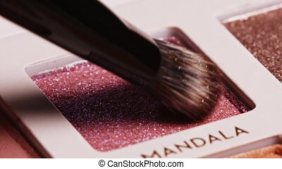 Brush gains satin duochrome on pile to be used in make-up. Artist working with eyeshadows palette. Macro view of working process, tools in beauty industry. Concept of decorative cosmetics, visagist.