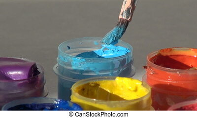 brush immersed in a jar of blue cyan Acrylic gouache paint....