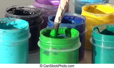 brush immersed in a jar of light green Acrylic gouache...