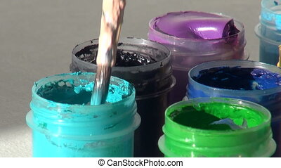 brush immersed in a jar of turquoise Acrylic gouache paint....