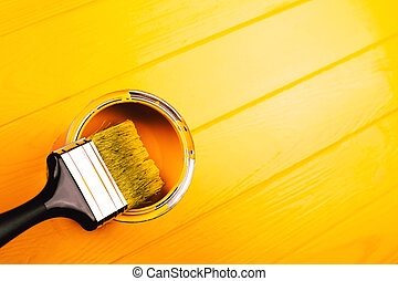 Brush in open can of yellow paint on freshly painted wooden board.