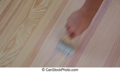 Brush in woman hand varnishes wooden table.