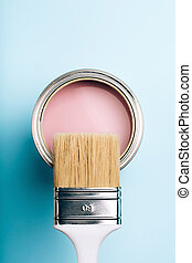 Brush on open can of pink paint on blue pastel background.