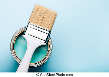Brush on open can of turquoise paint on blue pastel background.