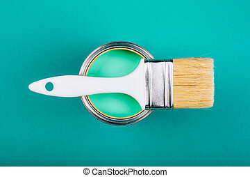 Brush on open can with turquoise color of paint on blue background.