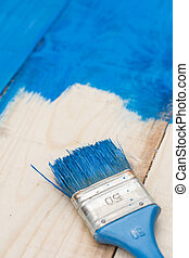 Brush painting with blue color on the wooden board planks
