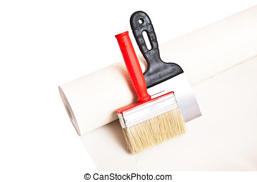 Brush, spatula and roll of wallpaper