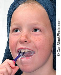Nine year old girl with towel on her wet hair brushing her teeth.