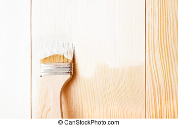 Brush with white paint on wooden background