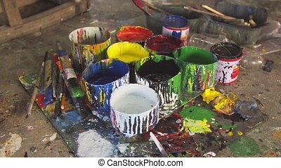 Brushes and Paint Arranged on the Floor in Artist Workshop...