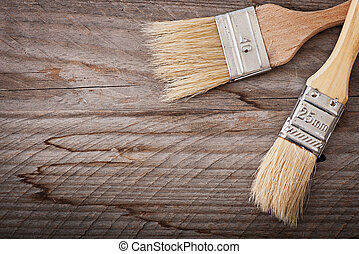 Brushes paint on the old wooden background