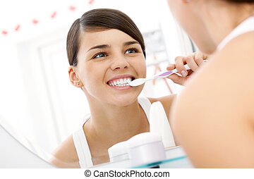 Image of pretty female brudhing her teeth in front of mirror in the morning