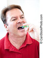 Brushing Teeth - Man brushing his teeth in the bathroom ...
