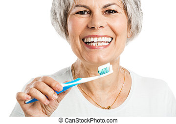 Brushing teeth - Portrait of a happy old woman brushing her...