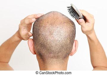 brushing thin hair - studio shot of a man doing scalp...