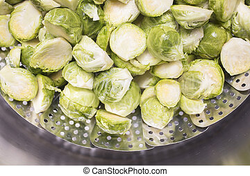 Brussel Sprouts in a steaming rack inside of a pot for cooking