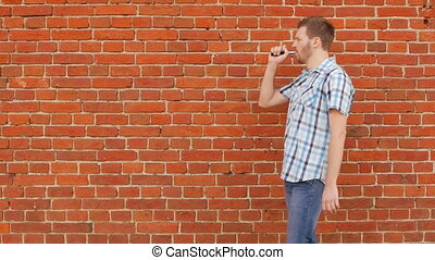 Brutal and fashionable man smokes vape against a brick wall...